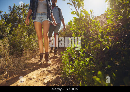 Hikers walking through country trail. Two young people hiking on mountains on sunny day. Cropped shot focus on legs. - Stock Photo