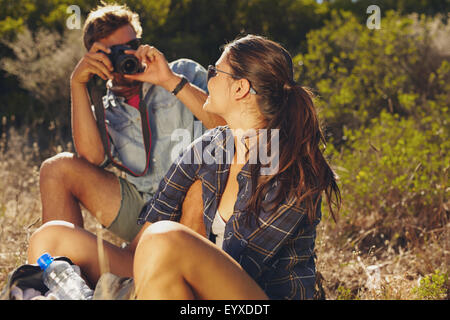 Young man taking pictures of his girlfriend while on hiking trip. Couple sitting and relaxing, taking a break. - Stock Photo
