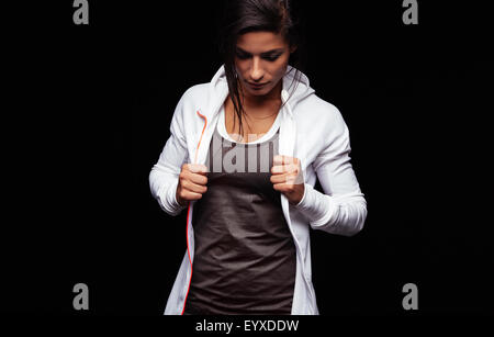 Portrait of fit young woman in sportswear standing on black background looking down. Caucasian fitness model holding - Stock Photo