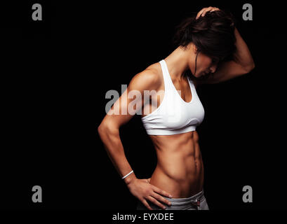 Image of fit young woman in sports wear looking down while standing on black background. Muscular fitness model - Stock Photo
