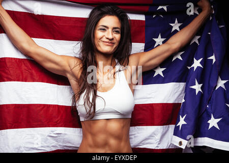 Portrait of happy young woman in sportswear holding American flag smiling. Fit american female athlete wrapped in - Stock Photo
