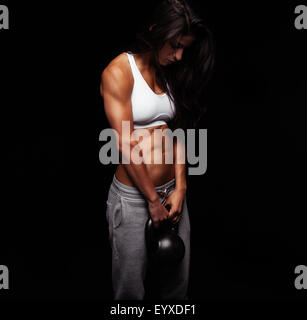 Young woman exercising crossfit with kettle bell weight. Crossfit female working out on black background. - Stock Photo