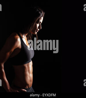 Image of fitness woman in sports clothing looking away on black background. Young female with perfect muscular body. - Stock Photo
