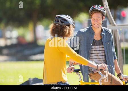 Man and woman with bicycles wearing helmets and talking in park - Stock Photo