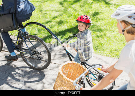 Portrait smiling boy riding tandem bicycle with father in park - Stock Photo