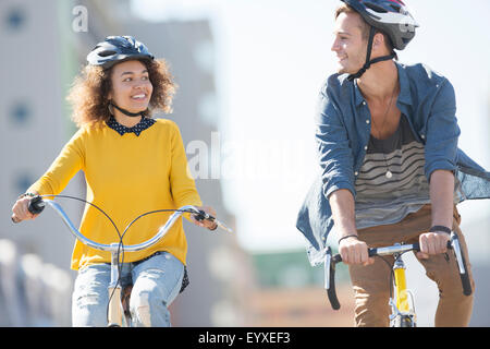 Young couple with helmets riding bicycles in city - Stock Photo