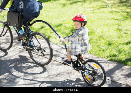 Boy riding tandem bicycle with businessman father in sunny park - Stock Photo