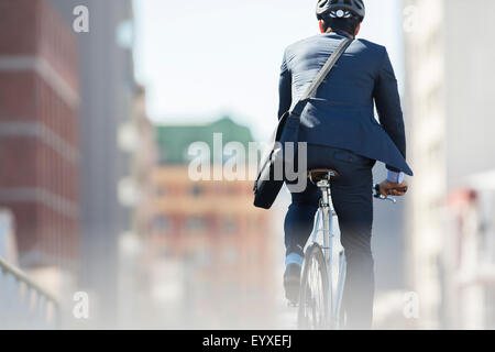 Businessman in suit and helmet riding bicycle in city - Stock Photo