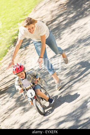Mother pushing son with helmet on bicycle in sunny park - Stock Photo