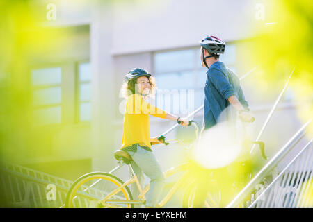 Man and woman with helmets on bicycles talking - Stock Photo