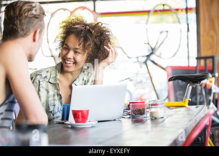 Couple talking at laptop in cafe - Stock Photo