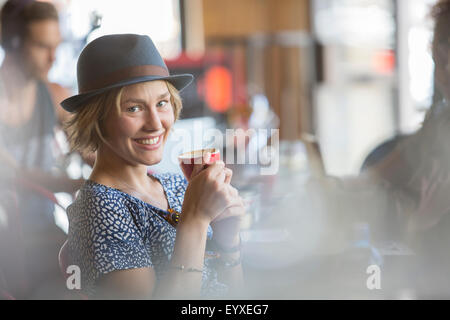 Portrait smiling woman in hat drinking espresso in cafe - Stock Photo