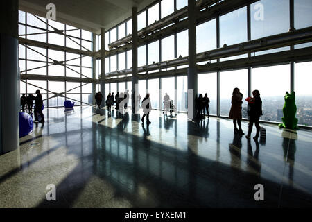 People's silhouette at the top of Lombardy building, Milan, Italy - Stock Photo