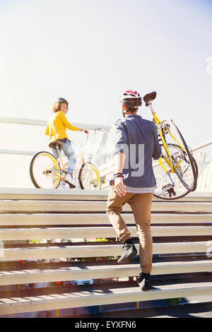 Man in helmet carrying bicycle up urban stairs - Stock Photo