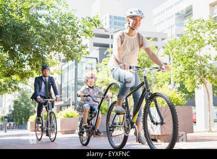 Mother and son in helmets riding tandem bicycle in urban park - Stock Photo