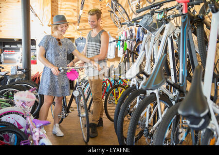 Couple eyeing bicycle in bicycle shop - Stock Photo