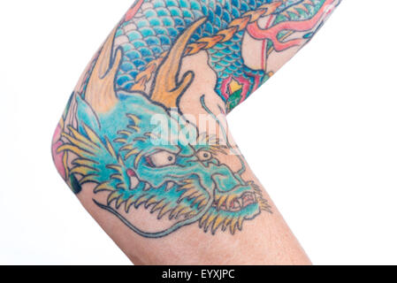 A detailed shot of a blue/green dragon tattoo in Japanese style on the forearm, elbow and bicep of a white male - Stock Photo