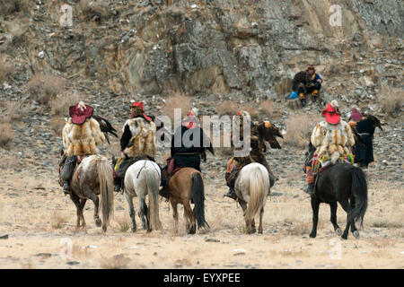Kazakh eagle hunters from the rear, facing the mountain that their eagles will be released from, Eagle Festival, - Stock Photo