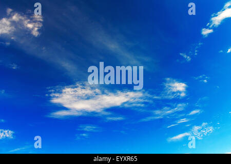 Clear Blue Sky Background. some white puffy clouds pops out on a beautiful blue sky - Stock Photo