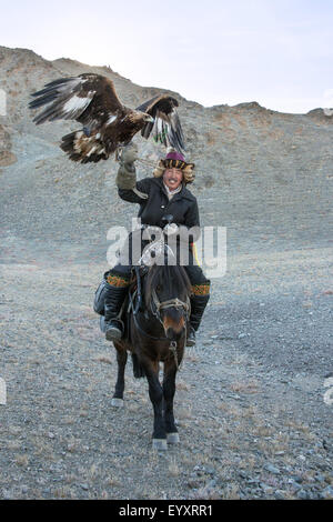 Kazakh eagle hunter with his un-hooded golden eagle held high #3, on the steppes of Western Mongolia, west of Olgii - Stock Photo
