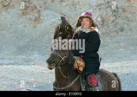 Kazakh eagle hunter with his hooded golden eagle on the steppes of Western Mongolia, west of Olgii - Stock Photo