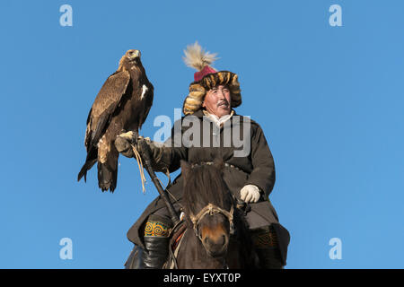 Elder eagle hunter bracing his heavy eagle on a crutch, west of Olgii, Western Mongolia - Stock Photo