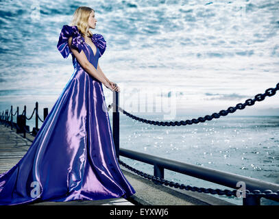 Young blond woman wearing a beautiful long blue dress, evening gown, standing at waterfront looking at the sea - Stock Photo