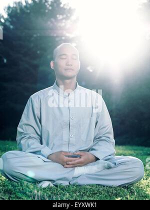 Shaolin monk meditating outdoors during sunrise in sunlight - Stock Photo
