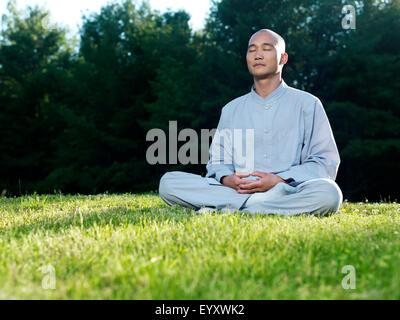Shaolin monk meditating outdoors during sunrise sitting on green grass - Stock Photo