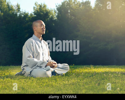 Shaolin monk meditating outdoors in the nature during sunrise sitting on grass in sunlight - Stock Photo