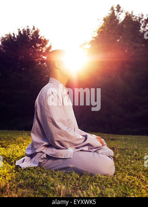 Shaolin monk meditating outdoors with sun rising behind him, artistic enlightenment concept - Stock Photo