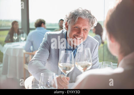 Smiling couple drinking wine in sunny restaurant - Stock Photo