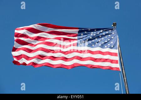 American flag on the blue sky, USA. - Stock Photo