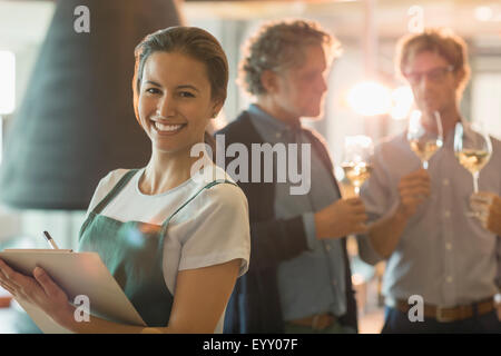 Portrait smiling woman with clipboard working in wine tasting room - Stock Photo