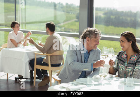 Couple toasting wine glasses in sunny winery dining room - Stock Photo