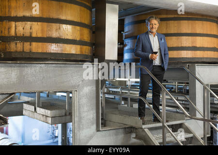 Portrait confident vintner with red wine on platform in winery cellar - Stock Photo