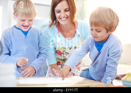 Mother and sons baking in kitchen - Stock Photo