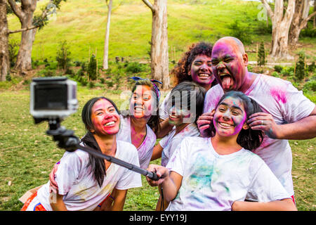 Friends covered in pigment powder using selfie stick - Stock Photo