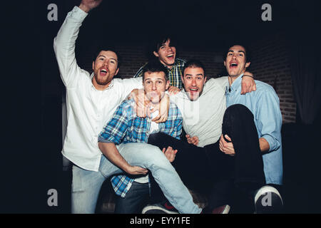 Laughing men playing at party at night - Stock Photo