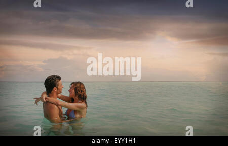 Caucasian couple swimming and hugging in ocean - Stock Photo