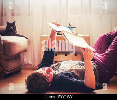 Caucasian man reading on living room floor - Stock Photo