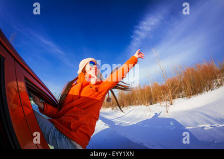 Caucasian woman leaning out car window in snowy field - Stock Photo
