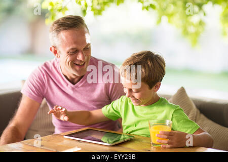 Caucasian father and son using digital tablet outdoors - Stock Photo