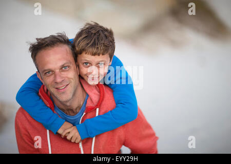 Caucasian father carrying son piggyback outdoors - Stock Photo