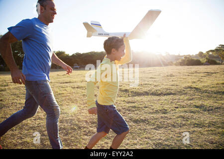 Caucasian father and son flying model airplane in field - Stock Photo