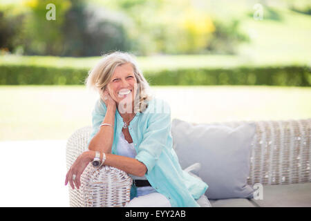 Caucasian woman sitting on sofa outdoors - Stock Photo