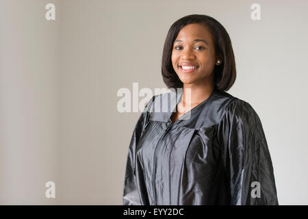 Mixed race graduate smiling in graduation robe