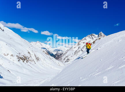Man skiing on snowy slope in remote landscape - Stock Photo