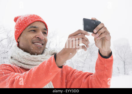 Black man using cell phone in snow - Stock Photo