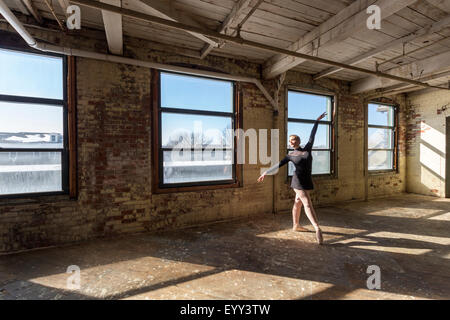 Caucasian ballet dancer performing in sunny loft - Stock Photo